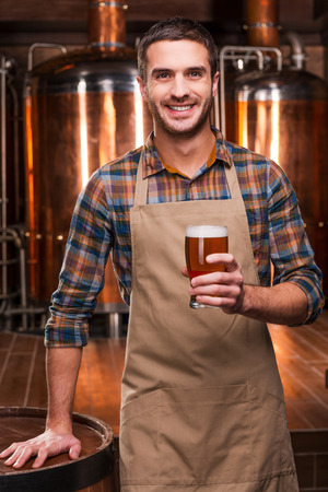 brewery: Brewing the best beer. Happy young male brewer in apron holding glass with beer and smiling while standing in front of metal containers