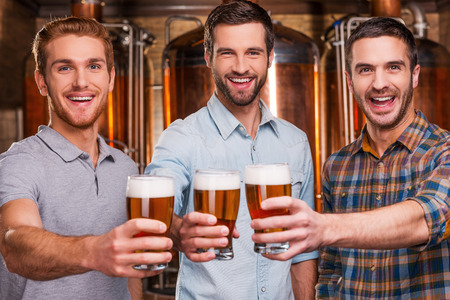 drinks after work: Cheers to you! Three cheerful young men in casual wear stretching out glasses with beer and smiling while standing in front of metal containers