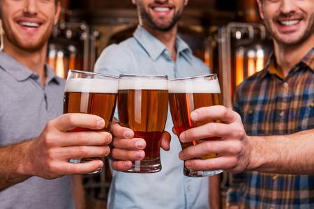 hombre tomando cerveza: �Salud! Primer plano de tres j�venes alegres en la ropa de sport de estiramiento a cabo vasos con cerveza y sonriendo mientras est� de pie delante de los envases met�licos Foto de archivo