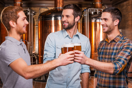 Cheers to us! Three cheerful young men in casual wear toasting with beer and smiling while standing in brewery in front of metal containers photo
