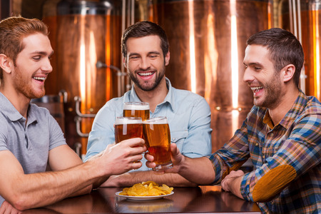 metal bars: Meeting old friends in bar. Three happy young men in casual wear toasting with beer and smiling while sitting in beer pub together