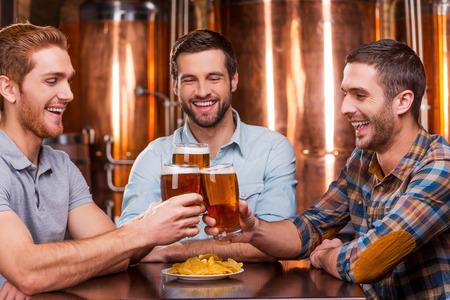 barra: Reuni�n viejos amigos en el bar. Tres hombres j�venes felices en ropa casual, brindando con cerveza y sonriendo mientras est� sentado en el pub cerveza juntos