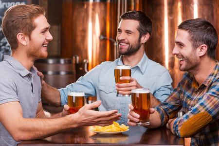 hombre tomando cerveza: Pasar buen rato con los amigos. Tres hombres jóvenes felices en ropa casual, hablando y bebiendo cerveza mientras estaba sentado en el pub cerveza juntos Foto de archivo