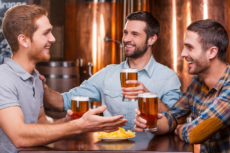 Spending great time with friends. Three happy young men in casual wear talking and drinking beer while sitting in beer pub together Stock Photo