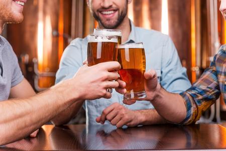 hombre tomando cerveza: Reuni�n amigos Vieja. Primer plano de tres j�venes felices en ropa de sport brindando con cerveza mientras estaba sentado en el pub cerveza juntos