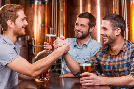 drinks after work: Spending great time with friends. Three happy young men in casual drinking beer while sitting in beer pub together