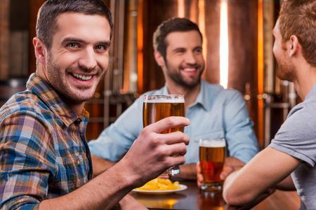 jovenes tomando alcohol: Pasar tiempo con los amigos. Apuesto joven brindando con cerveza y sonriendo mientras estaba sentado con sus amigos en el pub de la cerveza