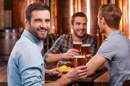 最高の友人と時間を過ごす。ビールで乾杯し、ビールのパブで友人達と座っている笑顔のハンサムな若者