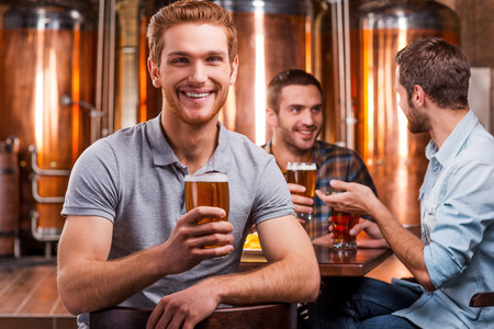 Spending time in beer pub. Handsome young man toasting with beer and smiling while his friends talking in the background photo