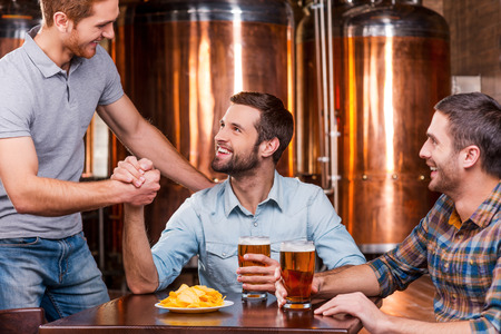 an old friend: Meeting old friend. Three happy young men sitting in beer pub together while two of them handshaking