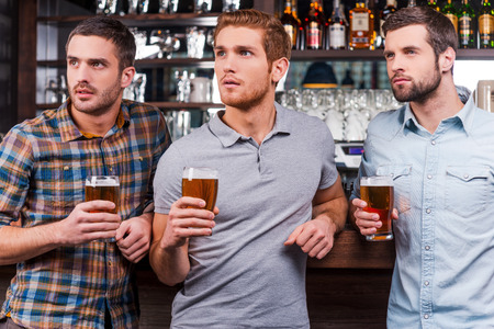 Watching football at the bar. Three handsome young men in casual wear holding glasses with beer and looking away while standing at the bar counter photo