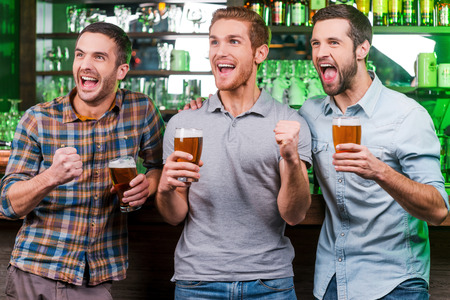 beer after work: Goal! Three happy young men in casual wear holding glasses with beer and gesturing while standing at the bar counter and looking away
