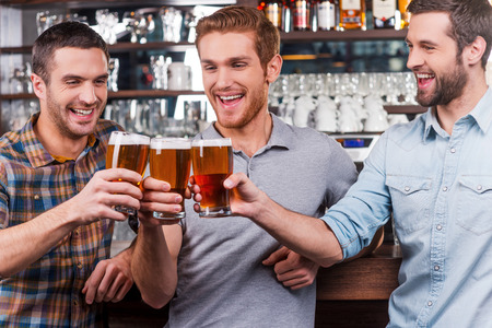 man drinking beer: Cheers to us! Three happy young men in casual wear toasting with beer and smiling while standing at the bar counter together