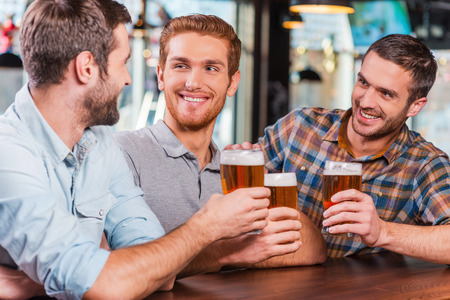 beer after work: Relaxing after work. Three happy young men in casual wear talking and drinking beer while sitting at the bar counter together