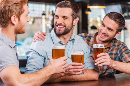 hombre tomando cerveza: Amigos en el bar. Tres hombres j�venes felices en ropa casual, hablando y bebiendo cerveza mientras estaba sentado en la barra del bar junto Foto de archivo
