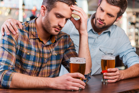 drinking alcohol: Consoling his depressed friend. Depressed young man sitting at the bar counter and holding head in hand while being consoled by his friend sitting near him Stock Photo