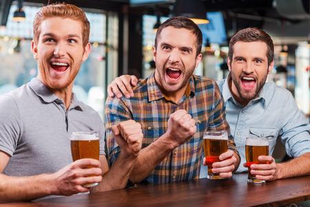 hombre tomando cerveza: Es una meta! Tres hombres jóvenes felices en ropa casual sosteniendo vasos con cerveza y aplaudir mientras ve el partido de fútbol en el bar junto Foto de archivo