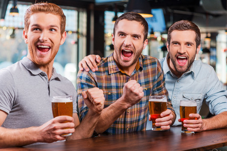 It is a goal! Three happy young men in casual wear holding glasses with beer and cheering while watching football match in bar together Фото со стока