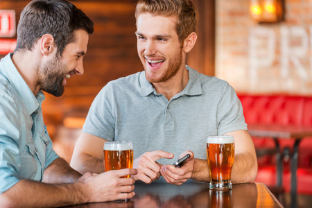 pub food: Just look at this photo! Two happy young men in casual wear drinking beer in pub while one of them holding smart phone and pointing it with smile
