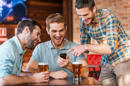 drinks after work: Friends having fun. Three happy young men in casual wear drinking beer in pub while one of them pointing smart phone and smiling