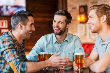 Ontmoeting met de beste vrienden. Drie gelukkige jonge mannen in vrijetijdskleding praten en het drinken van bier tijdens de vergadering in de bar bij elkaar
