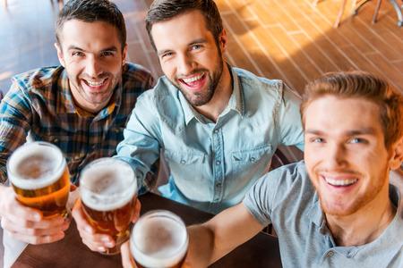 hombre tomando cerveza: �Salud! Vista superior de tres hombres j�venes felices en ropa casual, brindando con cerveza mientras estaba sentado en el bar junto Foto de archivo
