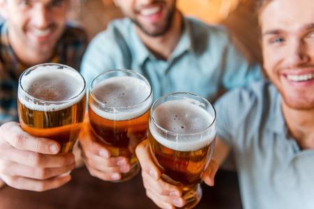 hombre tomando cerveza: Saludos para el �xito! Vista superior de tres hombres j�venes felices en ropa casual, brindando con cerveza mientras estaba sentado en el bar junto Foto de archivo