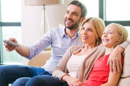 mujer viendo tv: Ver la televisi�n juntos. Familia feliz de tres uni�n entre s� y sonriendo mientras est� sentado en el sof� y viendo la televisi�n juntos