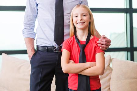ni�os vistiendose: Orgullosa de su padre. Ni�a alegre en la corbata de pie cerca de su padre y mantener los brazos cruzados Foto de archivo