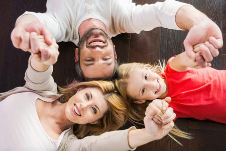 happy family: Familia feliz junto. Vista superior de la familia feliz de tres uni�n entre s� y sonriendo mientras est� acostado en el piso de madera