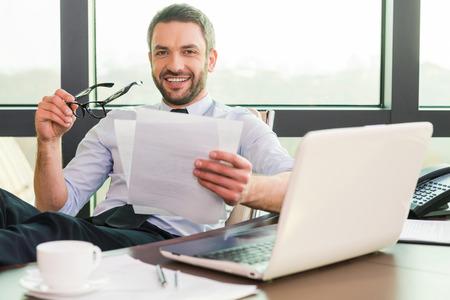 empleado de oficina: �En qu� puedo ayudarle? Hombre maduro hermoso en camisa y corbata ajustando sus gafas y sonriendo mientras sentado en su lugar de trabajo Foto de archivo