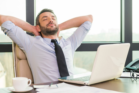 Taking time for a break. Handsome mature man in shirt and tie holding hands behind head and keeping eyes closed while sitting at his working place