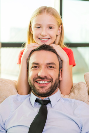 girl bonding: Me and my father. Cute little girl bonding to her cheerful father sitting on the couch at home