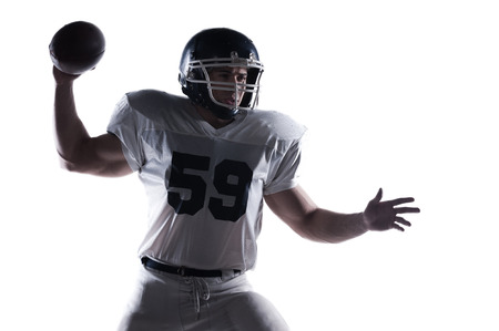 decisive: Decisive shot.  American football player throwing ball standing against white background