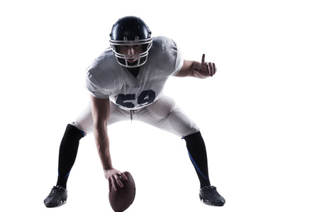 player: American football player getting ready before throwing ball while standing against white background Stock Photo