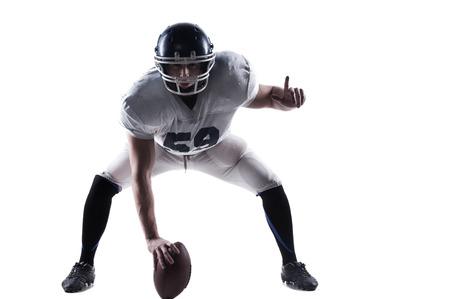 jugador de futbol americano: Jugador de f�tbol americano prepar�ndose antes de tirar el bal�n mientras est� de pie contra el fondo blanco