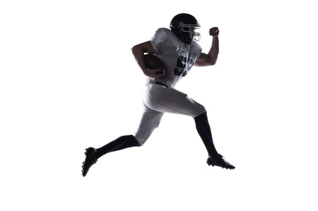 football player: Side view of American football player holding ball and jumping against white background
