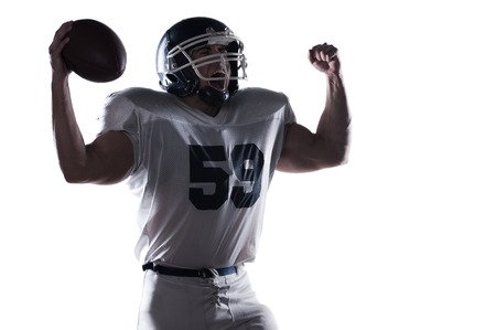 football silhouette: American football player screaming and keeping arms raised while standing against white background