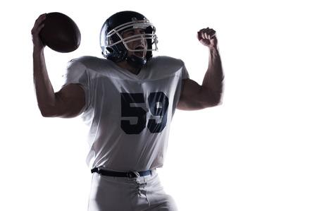 jugador de futbol: Jugador de f�tbol americano gritando y manteniendo los brazos en alto mientras est� de pie contra el fondo blanco