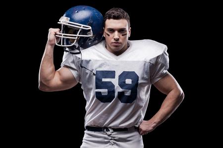 jugador de futbol: �l est� listo para ganar! Jugador de f�tbol americano que mira la c�mara y llevar casco en su hombro mientras est� de pie contra el fondo negro