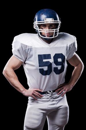 jugador de futbol americano: Jugador de f�tbol americano que mira la c�mara y la celebraci�n de las manos en las caderas de pie contra el fondo negro Foto de archivo