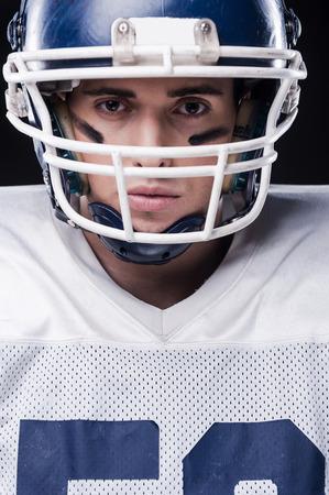 jugador de futbol: Retrato de jugador de f�tbol americano que mira la c�mara mientras est� de pie contra el fondo negro