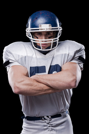american football background: Portrait of American football player looking at camera and keeping arms crossed while standing against black background Stock Photo