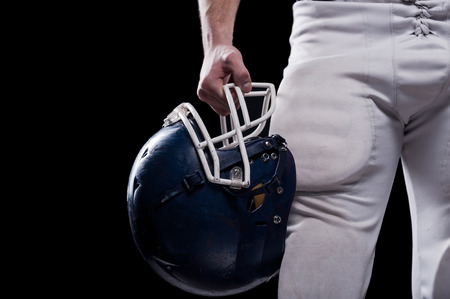 Cropped image of American football player holding football helmet while standing against black background