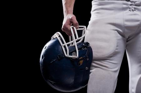futbolista: Recorta la imagen de jugador de f�tbol casco celebraci�n de f�tbol americano mientras est� de pie contra el fondo negro