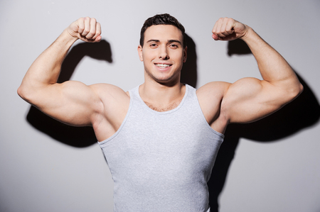 only the biceps:  Young muscular man showing his biceps and smiling while standing against grey background Stock Photo