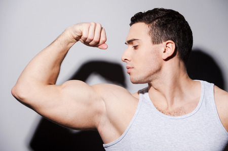 only the biceps: Handsome young muscular man showing his bicep on one hand while standing against grey background