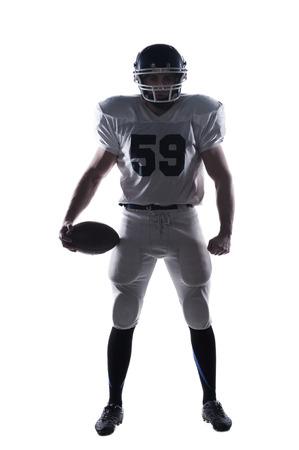 hombre deportista: Longitud total de jugador de f�tbol americano que sostiene la bola y mirando ay c�mara de pie contra el fondo blanco
