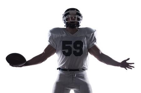 jugador de futbol: Jugador de f�tbol americano gritando y manteniendo los brazos extendidos mientras est� de pie contra el fondo blanco