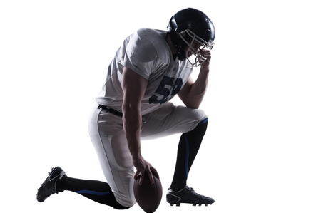 player: Side view of American football player holding hand on helmet while standing on knee against white background Stock Photo